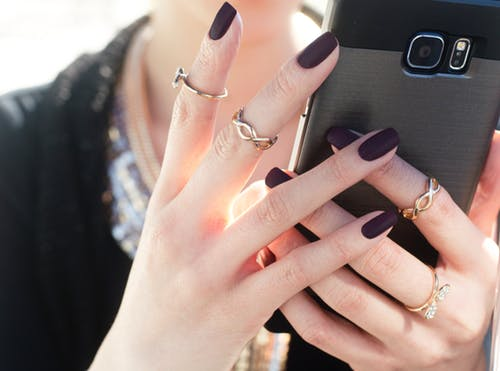 girl holding phone and wearing nailpolish